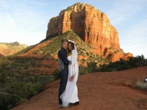 young couple standing in front of bell rock on a spiritual tour package in Sedona.